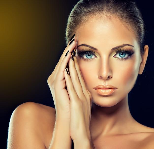Closeup portret van een jonge vrouw in een chique avond make-up, grote wimpers en vergulde nagellak met een elegant gebaar van haar hand