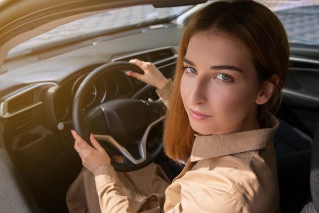 Closeup portret van een jonge vrouw zittend op de stoel van een bestuurder en loking over haar schouder