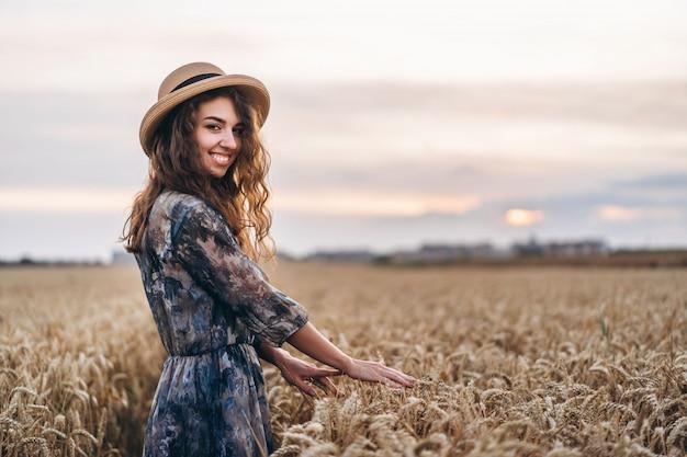 Closeup portret van een mooie jonge vrouw met krullend haar. vrouw in jurk en hoed staande in een tarweveld