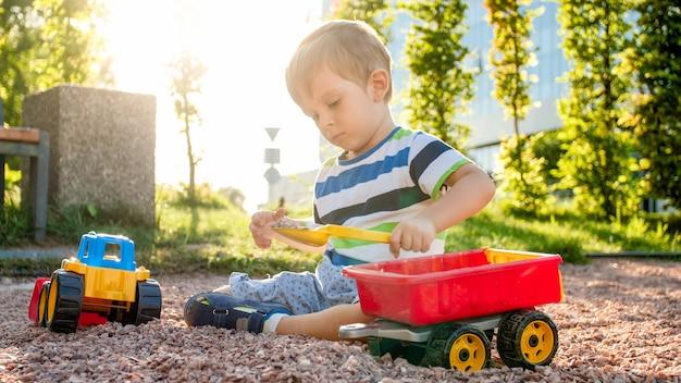 Closeup portret van gelukkig lachend 3 jaar oude kind jongen graven zand op de speelplaats met speelgoed plastic vrachtwagen of graafmachine. kind palying en plezier in het park in de zomer