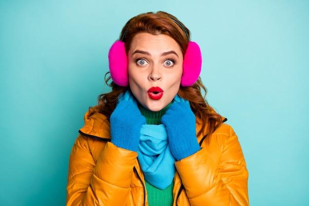 Closeup portret van geschokt reiziger dame rode lippen geweldige winterdag open mond goed nieuws dragen casual gele overjas blauwe sjaal roze oor covers.