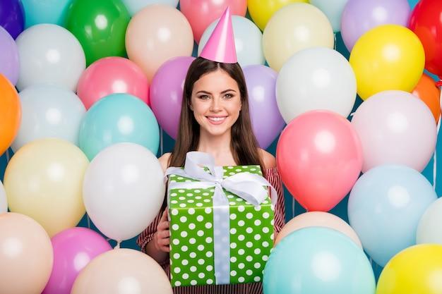 Closeup portret van haar ze mooi aantrekkelijk mooi vrij charmant blij vrolijk vrolijk langharig meisje in handen houden gestippelde geschenk onder kleurrijke luchtballen