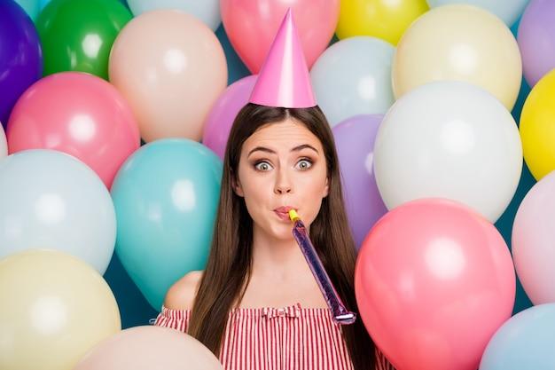 Closeup portret van haar ze mooie aantrekkelijke mooie vrij verbaasd grappig meisjesachtig vrolijk vrolijk langharig meisje blaast feestelijk fluitje met plezier tussen vele kleurrijke luchtballen