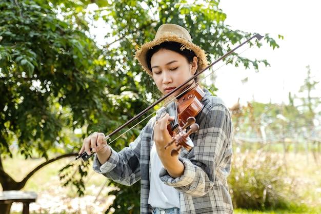 Closeup portret van jonge aziatische vrouw muziek violist spelen de viool ontspannen in de tuin