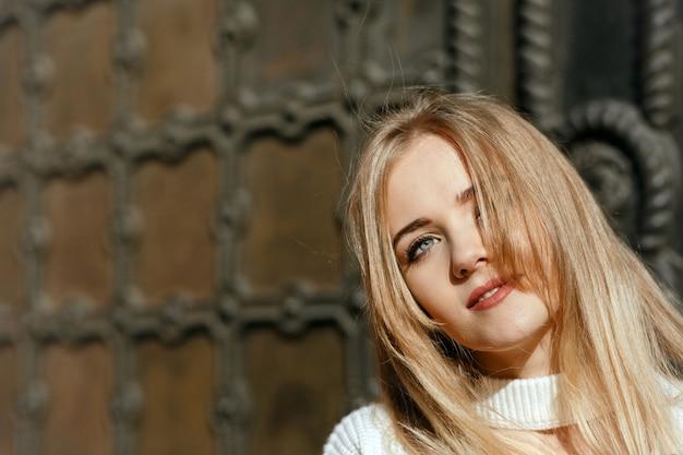 Closeup portret van jonge model met natuurlijke make-up poseren in de buurt van metalen smeedijzeren deur. ruimte voor tekst
