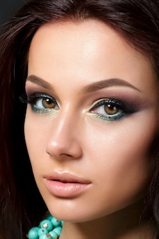 Closeup portret van jonge mooie vrouw met avond make-up dragen blauwe ketting. model poseren. smokey eyes met eyeliner. klassiek make-upconcept.