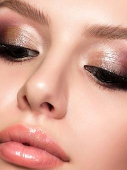 Closeup portret van jonge mooie vrouw met avond make-up. roze en gouden veelkleurige smokey eyes. luxe huidverzorging en modern mode-make-upconcept.