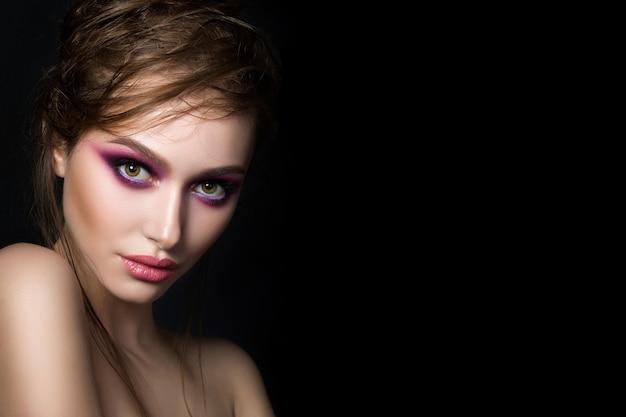 Closeup portret van jonge mooie vrouw met helder roze smokey eyes en lippen op zwarte achtergrond