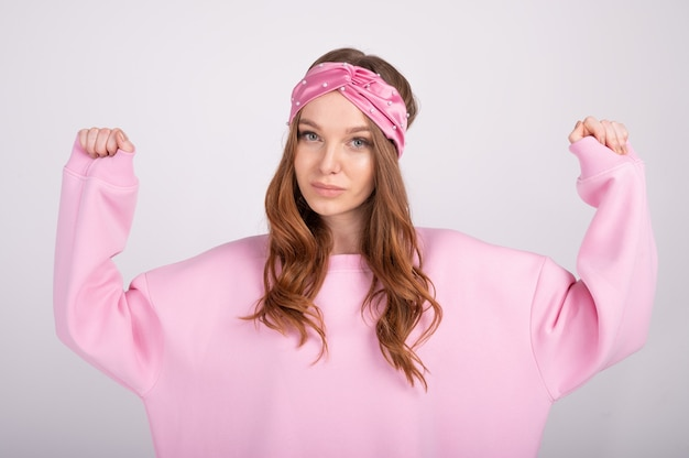 Closeup portret van jonge mooie vrouw met stijgende handen. trendy meisje in casual roze hoodie.