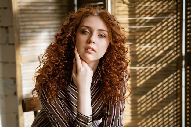 Closeup portret van jonge roodharige krullende vrouw met droevige ogen