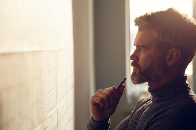 Closeup portret van knappe man geconcentreerd op werk architect werkzaam in kantoor met blauwdrukken en...