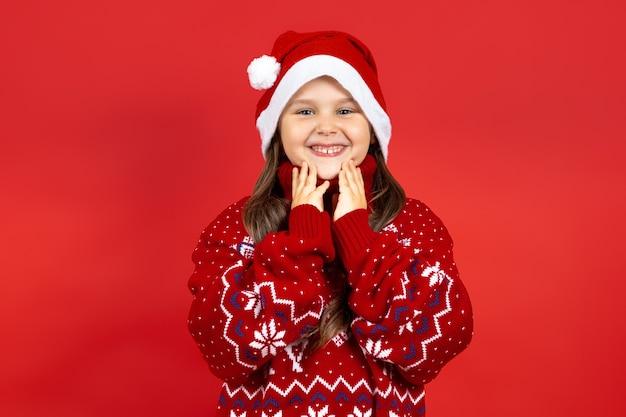 Closeup portret van lachend meisje in rode gebreide kerst trui met rendieren en kerstman hoed...