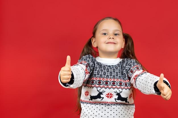 Closeup portret van lachend schattig meisje in witte kerst trui met rendieren duimen geven tot c...