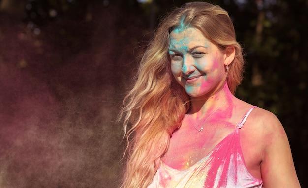 Closeup portret van lachende jonge vrouw bedekt met kleurrijke droge verf op holi festival van kleuren