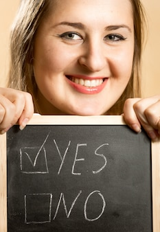 Closeup portret van lachende vrouw met bord met twee antwoorden
