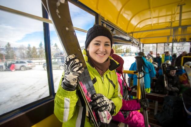 Closeup portret van lachende vrouw rijden in de bus met ski's
