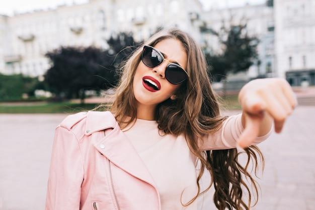 Closeup portret van meisje met lang kapsel in zonnebril wijzend op camera in stad.