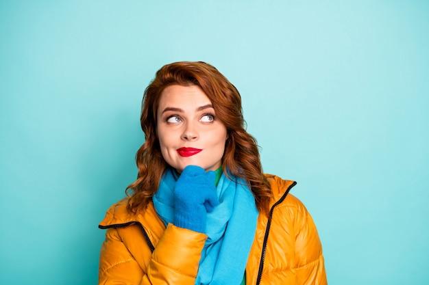 Closeup portret van mooie dame opzoeken lege ruimte denkbeeldige vlucht arm op kin dragen gele overjas blauwe sjaal groene coltrui.