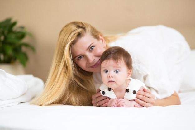 Closeup portret van mooie jonge moeder met lang blond haar knuffelen met haar schattige baby