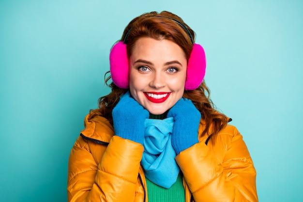 Closeup portret van mooie reiziger dame rode lippen genieten van geweldige winterdag klaar voor wandeling dragen casual gele overjas blauwe sjaal roze oorbeschermers.