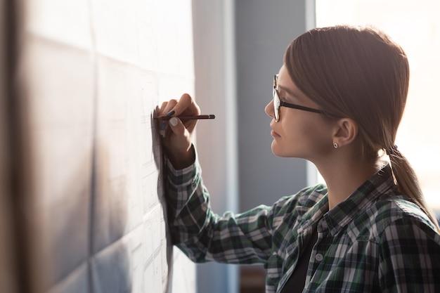 Closeup portret van mooie vrouw geconcentreerd op werk architect werkzaam in kantoor met blauwdrukken...