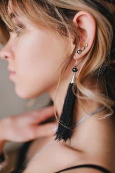 Closeup portret van mooie vrouw met krullend haar, stijlvolle zwarte outfit.