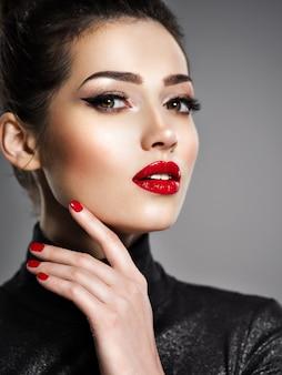 Closeup portret van mooie vrouw met lichte make-up en rode nagels. sexy jong volwassen meisje met rode lippenstift.