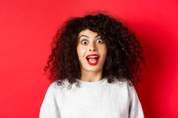 Closeup portret van opgewonden vrouw met krullend haar schreeuw verrast en verbaasd bij het controleren van speciale d...