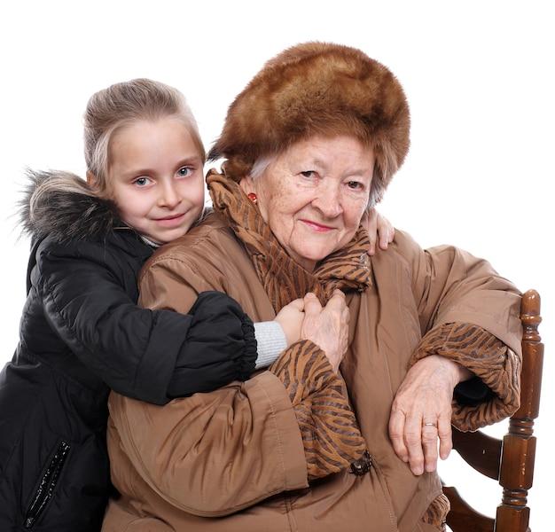 Closeup portret van oude vrouw met kleine kleindochter in winter uitloper geïsoleerd
