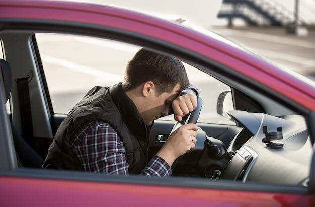 Closeup portret van overstuur man met stuurwiel steering