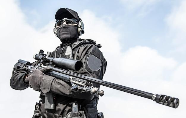 Closeup portret van politie speciale operaties sluipschutter in zwarte lege uniformen en masker, kogelvrije vesten, ballistische bril en koptelefoon staande op de hemelachtergrond, sluipschuttersgeweer met optische zicht houden