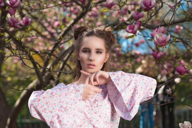 Closeup portret van prachtige brunette model staande in bloeiende magnoliatuin