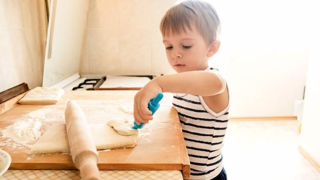 Closeup portret van schattige 3 jaar oude peuter jongen koekjes bakken en deeg rollen met houten rooling pin. kleine chef-kok
