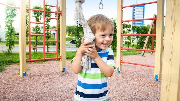 Closeup portret van schattige lachende gelukkig jongetje op kinderspeelplaats in park at