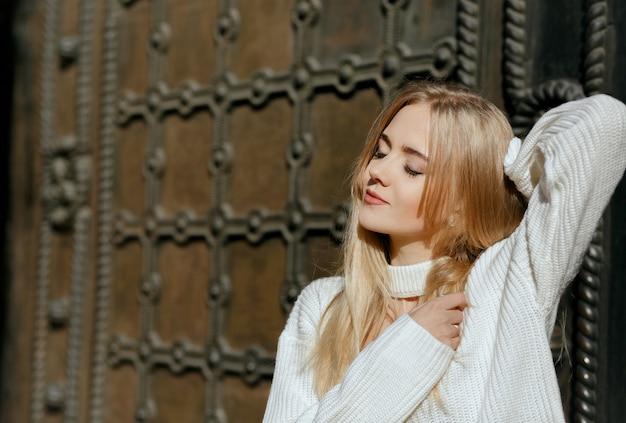 Closeup portret van sensueel meisje met natuurlijke make-up poseren in de buurt van metalen smeedijzeren deur. ruimte voor tekst