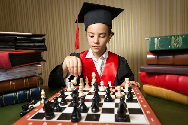 Closeup portret van slim meisje in afstuderen pet schaken