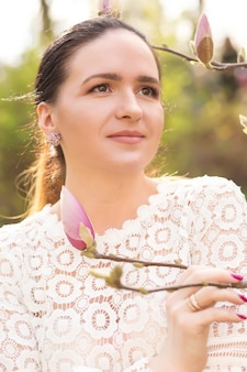 Closeup portret van teder brunette model met naakt make-up poseren in de buurt van de bloeiende magnolia bloemen