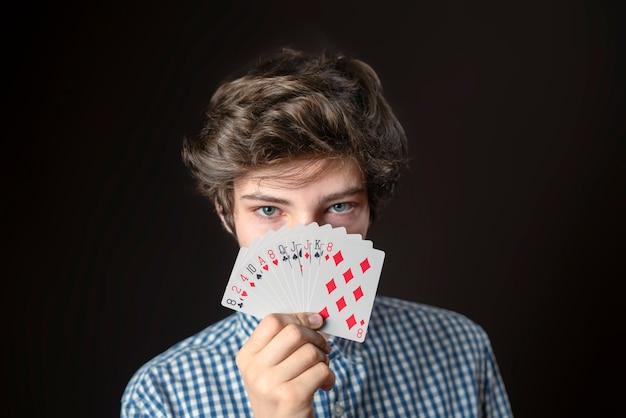 Closeup portret van tiener mannelijke greep gokkaart laat het zien en bedek gezicht b