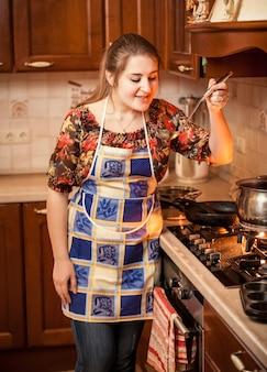 Closeup portret van vrouw die soep met pollepel probeert