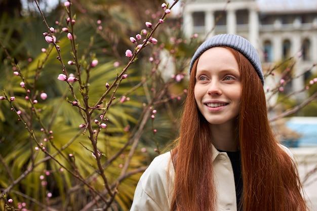 Closeup portret van vrouw in lentetuin lente trendy roodharige vrouw geniet van de geur van b...