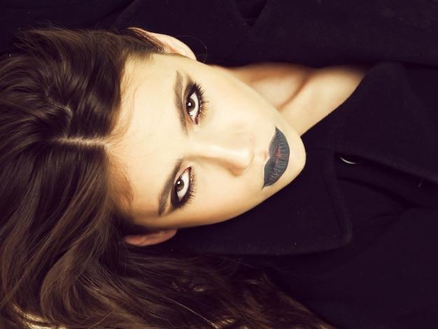Closeup portret van vrouw in zwarte jas, mooie mode meisje met modieuze make-up op gezicht en lippen.