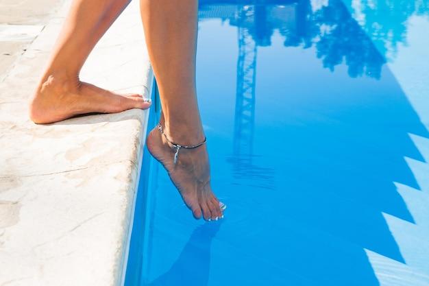 Closeup portret van vrouwelijke benen in de buurt van zwembad