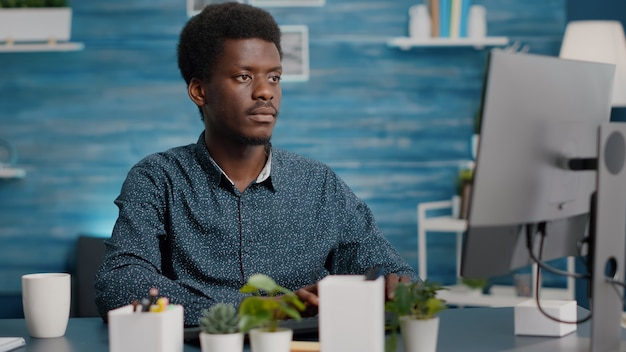 Closeup portret van zwarte afro-amerikaanse man aan het werk op de computer in de woonkamer, glimlachend in de camera. externe internet online webmanager die vanuit huis werkt en sociale afstand houdt