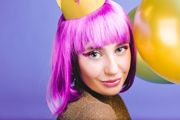 Closeup portret verbazingwekkende vrolijke jonge vrouw met gesneden paars haar, gouden kroon en ballonnen carnaval, nieuwjaarsfeest vieren. charmante glimlach, make-up met tinsels, geluk.
