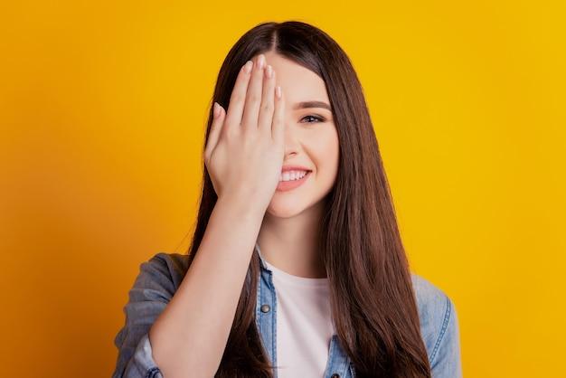 Closeup portret vrouw lachend palm dekking half gezicht geïsoleerde gele muur achtergrond
