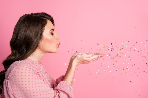Closeup profiel zijaanzicht portret van schattig meisje waait confetti lucht kus