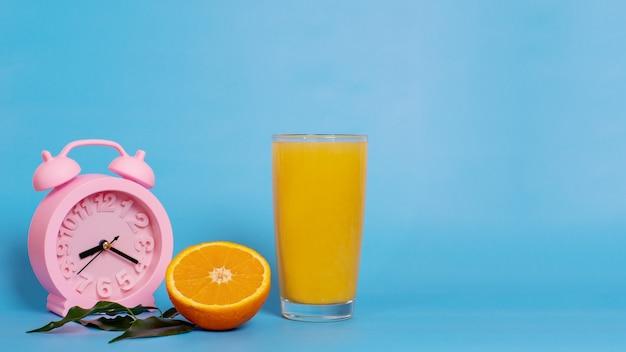 Closeup roze wekker met glas sinaasappelsap en vers rijp fruit in tweeën gesneden op een blauwe achtergrond. ontbijt eten of drinken in de ochtend. biologisch en gezond ontbijtconcept.