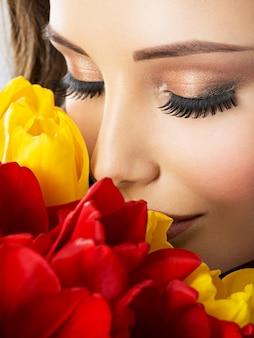 Closeup schoonheid gezicht van de jonge vrouw met bloemen. aantrekkelijk model met rode en gele tulpen
