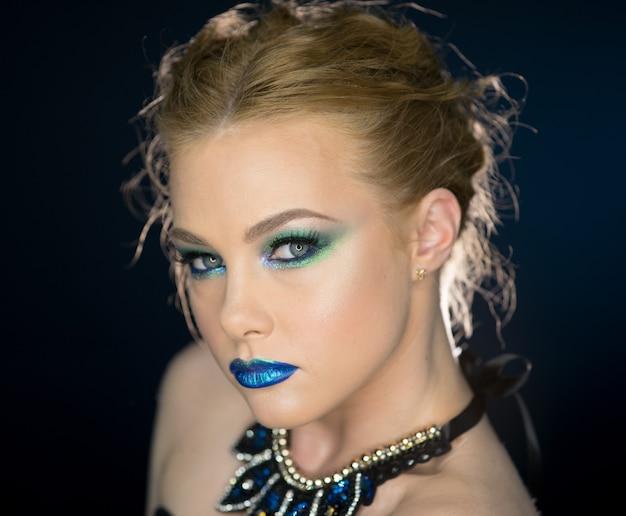 Closeup schoonheid portret van aantrekkelijk model gezicht met helder gezicht. veelkleurige oogmake-up en roze lippenmake-up