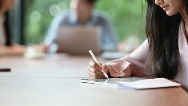 Closeup secretaris vrouw schrijft op een computertablet zittend in de vergaderzaal.